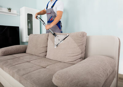 Male Worker Cleaning Sofa With Vacuum Cleaner